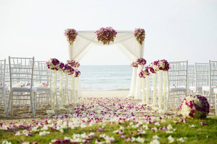 Stunning bamboo archway, beautifully decorated in fresh flowers for a beach wedding. Designed By Toom
