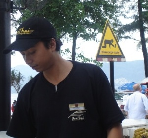 Funny photo of the Drunken People Crossing Sign behind the bartenders shoulder at a bar in Patong.