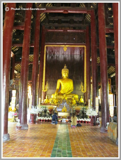 Buddha image inside with smaller seated Buddha images in front.