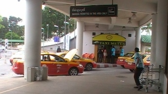 Turn right when exiting the arrival area to find the local red and yellow taxi service.